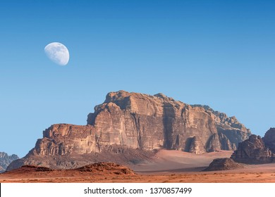 incredible lunar landscape with huge moon in Wadi Rum village in the Jordanian red sand desert. Wadi Rum also known as The Valley of the Moon,  Jordan - Image