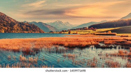 Incredible Nature Landscape. Colorful sky Resia Lake in Dolomites mountains, during sunrise. Scenic image of Stunning nature in Dolomites alps. Amazing Autumn Landscape. Natural background.