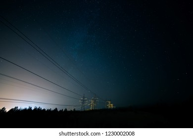 Incredible night sky with stars, Milky Way passing over power line in long exposure timelapse. Beautiful panorama view. Nature in the countryside. Astro photography