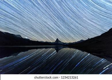 Incredible night view of Stellisee lake with Matterhorn Cervino peak in Swiss Alps. Stars trails moving in blue sky. Zermatt resort location, Switzerland. Landscape astrophotography