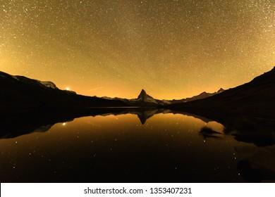 Incredible night view of Stellisee lake with Matterhorn peak in Swiss Alps. Millions of stars in the pre-bright sky. Zermatt location, Switzerland. Landscape astrophotography