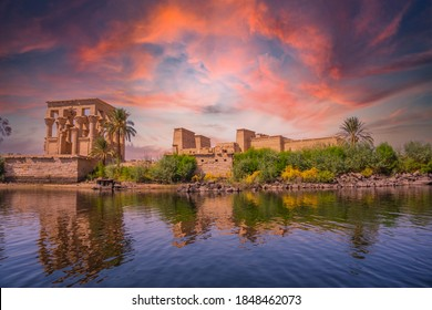 Incredible orange sunrise at the temple of Philae, a Greco-Roman construction seen from the Nile river, a temple dedicated to Isis, goddess of love. Aswan. Egyptian