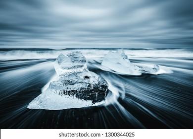 Incredible piece of the iceberg sparkle on black sand. Location Jokulsarlon lagoon, Diamond beach, Vatnajokull national park, Iceland, Europe. Long exposure photography. Discover the beauty of earth.