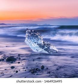 Incredible pieces of the iceberg sparkle on famous Diamond Beach at  Jokulsarlon lagoon during sunset. Location : Jokulsarlon lagoon, Diamond beach, Vatnajokull national park, Iceland, Europe