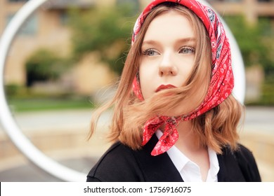 Incredible portrait of a fashionable girl in a red scarf and red lips. Fashion for hats. The blonde with a square walks in the park. Slovenian girl, portrait.