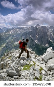 Incredible Prokletije mountains an a older hiker on top with a big backpack