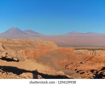 The incredible red rocks of the Moon Valley (Valle de la luna) near San Pedro De Atacama at sunset, with andean volcano Licancabur in the distance.