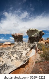 Incredible rock formations worn by millions of years of weathering by wind and rain set against a light clouds and an intense blue background in the Karoo, South Africa