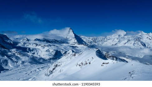 Incredible shot of a perfect view from Stockhorn over mountainous winter landscape with Gornerglacier and Matterhorn near Zermatt in the Swiss alps on bluebird February morning