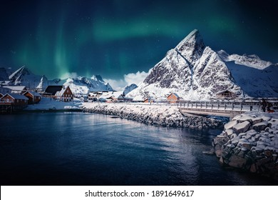 Incredible snowy winter landscape with Aurora borealis over Sakrisoy village. Lofoten islands. Norway. Vivid Northern lights during polar night above Reine fjord. Iconic location for  photographers
