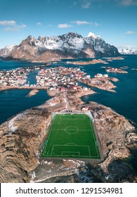 Incredible soccerfield sorrounded by water sea and mountains, Henningsvaer, Lofoten Islands, Norway