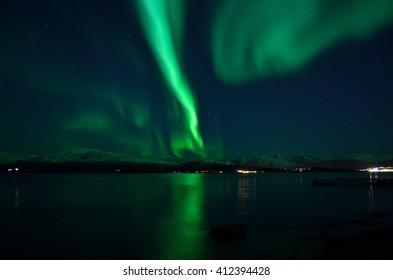 incredible strong aurora borealis over fjord and snowy mountain