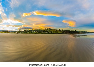 Incredible sunset on the Pacific coast, New Zealand. Clouds are reflected in the gentle ripples of the surf. The concept of active and ecotourism