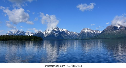 the incredible view of the grand teton range from the colter bay swimming beach  on a sunny summer day in grand teton national park, wyoming