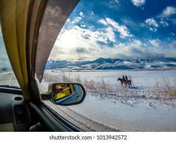Incredible view of mountain with people on horses captured on wide angle camera from a car.