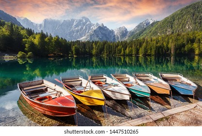 Incredible view on Fusine lake side. Scenic image of fairy-tale lake with boats on water and colorful sky. Wonderful Autumn scenery. Amazing nature Background. Awesome dramatic scene. Julian Alps