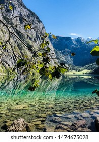 Incredible views of the mountains and the emerald lake. The water is so clear that the boundary between water and land is not visible. Photographed on hard-to-reach lake Obersee in Bavaria, Germany.
