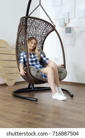 incredibly beautiful blond woman with slender legs in a checkered blue dress posing in a wicker chair rocking chair. rest and relaxation of young beauty