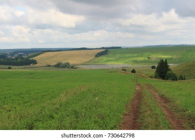 Incredibly beautiful landscape of the Russian plain. Farmlands and the vast expanses of nature. The sky is in the clouds and fresh air is far from the city. Rural fields