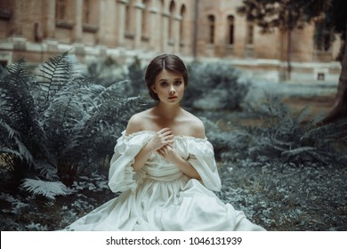 An incredibly beautiful princess sits in the castle garden amid the fern and moss. A beautiful, frightened face. Big sad eyes. Collected hair - a neat hair. On the lady - an old dress. Art photo