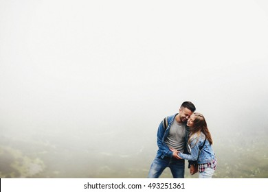 incredibly beautiful and young couple standing on the precipice of mountains