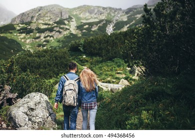 incredibly beautiful and young couple walking in the mountains