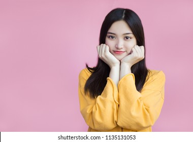 An incredibly cute girl in a yellow sweater on a pink background with black Asian hair. Lovely puffy cheeks, huge eyes and a keen smile. Having leaned on his hands and looks cute into the frame