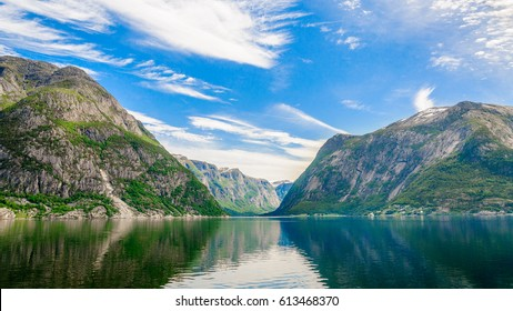 Incredibly landscape view on the mountain peaks with green slopes and the mirror surface of the water and wonderful feather clouds on the sky on background, Norway, Hardangerfjord