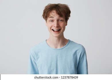 Incredibly, over-measure joyful guy smiles broadly, shows enthusiasm and passion, disheveled hair, mouth wide opened with braces on teeth, feels glad, over white background