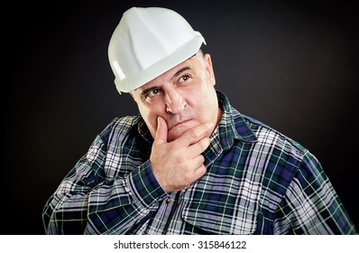 Incredulous worker with helmet. Hand on chin, black background.