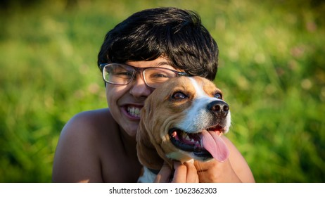 Indaiatuba, April 5, 2018 Close up of the face of an unidentified child hugging his dog on a sunny day with kills his back from an unidentified park