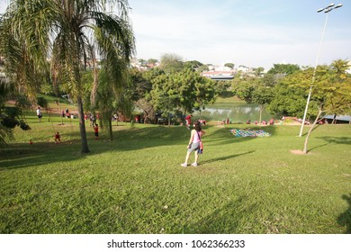 Indaiatuba April 5, 2018 Unidentified park well wooded with a large Lake in the background and a beautiful green lawn with a blue sky and some unidentified people strolling