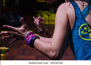 Indaiatuba, December 13, 2016, part of the arms and backs of two unidentified people in a class of zumba, making a sign, arms have bracelets, in an unidentified location