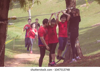 Indaiatuba March 16, 2018 unidentified children crossing a rope bridge trapped in two trees on a sunny day in an unidentified park with a faint red smoke