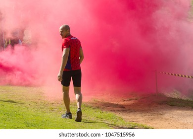 Indaiatuba March 16, 2018 Unidentified man running on a lawn in an unidentified park crossing a red smoke curtain