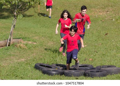 Indaiatuba March 16, 2018 Unidentified children running in an unidentified park passing on a row of tires Good sunny day