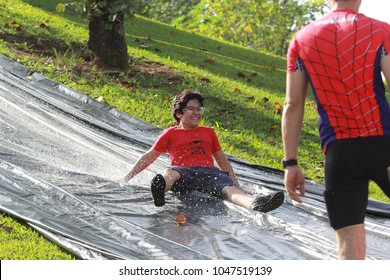 Indaiatuba March 16, 2018 unidentified child having fun descending Hill of grass covered with plastic and water in an unidentified park with an unidentified man looking at him