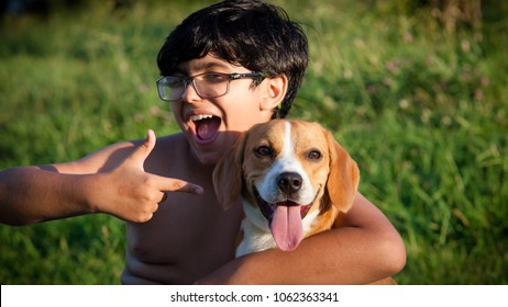 Indaiatuba on April 5, 2018 close up on the face of an unidentified child hugging his beagle bicolor dog on a sunny day with a green lawn background of an unidentified park