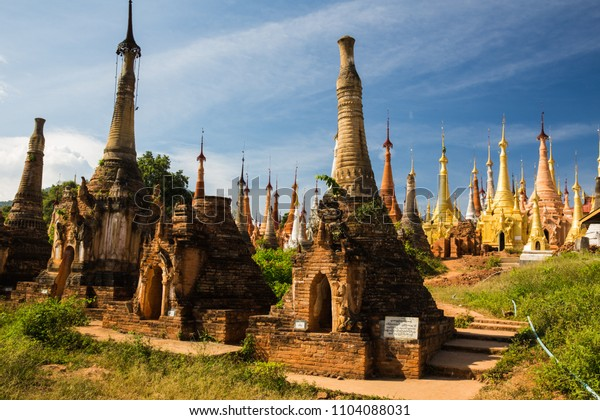 Indein Myanmar - Dec 2016: Visiting the outdoor part of the ancient pagoda at Shwe Indein Pagoda temple, with the recently restored gold pagoda at the other side