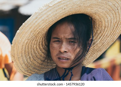 Indein, Myanmar - March 2019: portrait of a young Burmese woman in a big straw hat and tanaka on her face