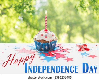 independence day, celebration and holidays concept - close up of glazed cupcake or muffin with burning candle and stars cofetti decoration on table at 4th july party over green natural background
