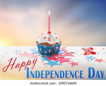 independence day, celebration, patriotism and holidays concept - close up of glazed cupcake or muffin with burning candle and stars cofetti on table at 4th july party over evening sky background