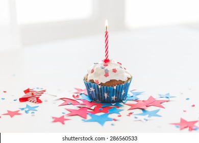 independence day, celebration, patriotism and holidays concept - close up of glazed cupcake or muffin with burning candle and stars cofetti decoration on table at 4th july party