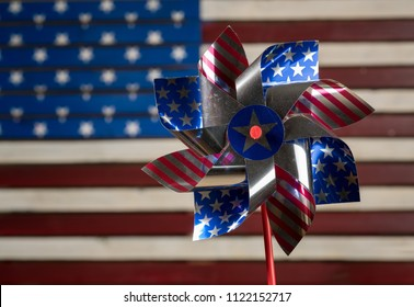 Independence day concept with pin wheel or whirligig in front of a USA Flag