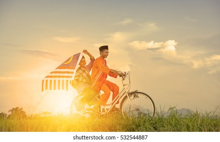 independence Day concept - Two happy young local boy riding old bicycle at paddy field holding a Malaysian flag with sunlight