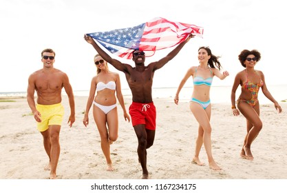 independence day, summer holidays and people concept - group of happy friends with american flag on beach