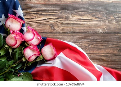 Independence Day USA concept. Memorial Day. Roses on the US flag flat lay top view