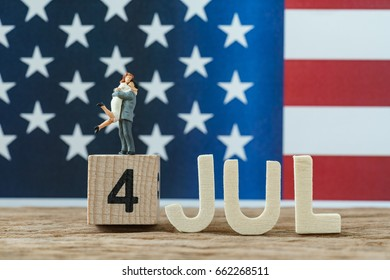 Independence day USA with miniature people young couple standing on wooden cube number 4 and alphabets JULY and United State national flag in the background.