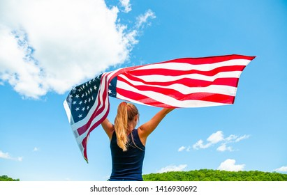 Independence Day. Young woman holding American flag on blue sky background. United States celebrate 4th of July