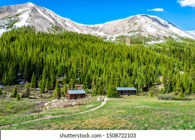 Independence Pass mining townsite buildings in White River National Forest in Colorado with green pine trees and snow mountain peaks